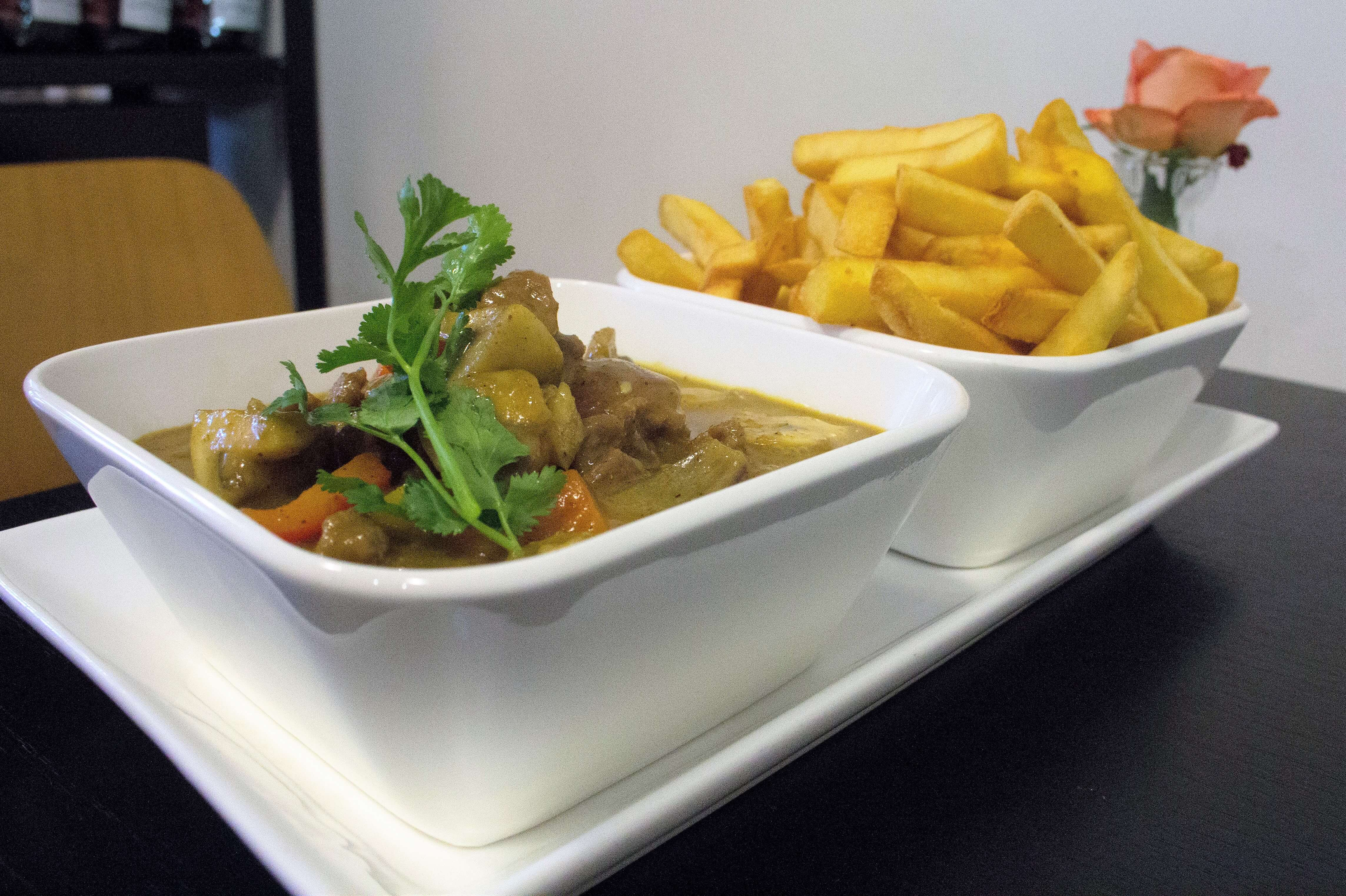 Beef Kandar Curry with chips. Dish on a table.